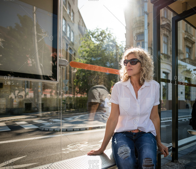 Stylish woman in sun glasses sitting on bus stop bench