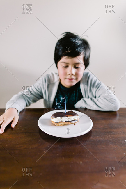 Young boy looking at a blown out birthday candle