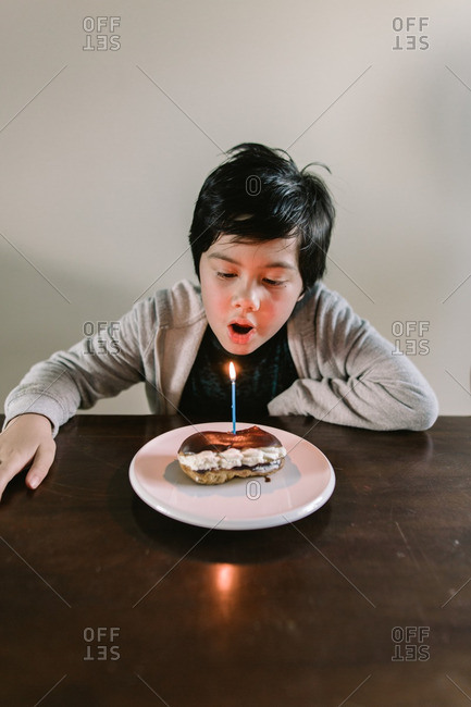 Young boy blowing out a birthday candle