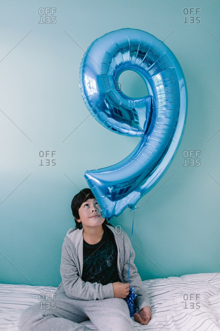 """Young boy holding a large """"9"""" balloon"""