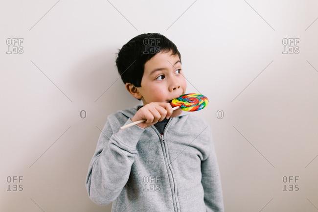 Young boy licking a rainbow lollipop