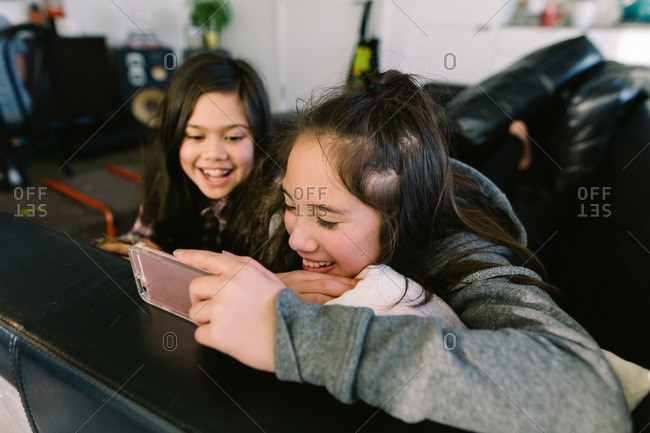 Two young girls watching a video on a smart phone
