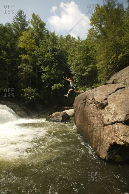 Woman leaps into the pool below Turtleback Falls on the Horsepasture River near Cashiers, NC.