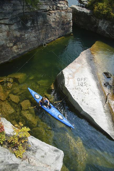 Summersville Lake, WV - August 25, 2005: Woman explores a rocky cove via kayak