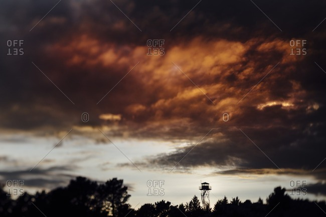Forest lookout tower at dramatic sunset with dark clouds