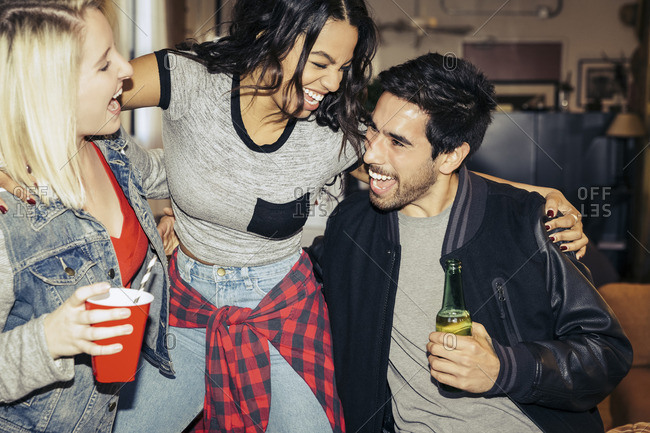 Three friends hanging out and laughing at a party
