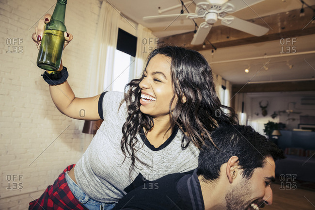 Young woman holding a beer and laughing with her friend at a party
