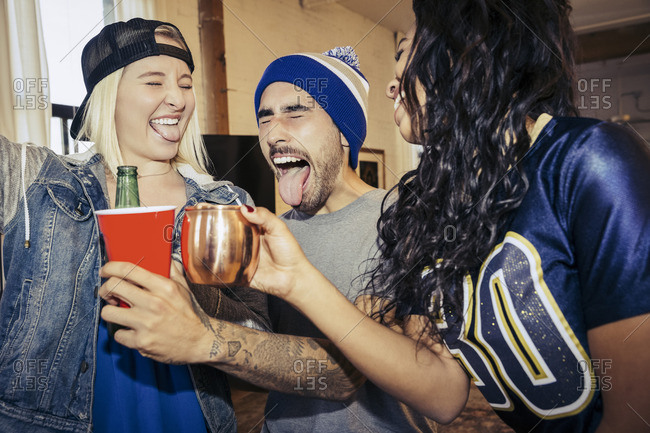 Three friends toasting and making silly faces at a party