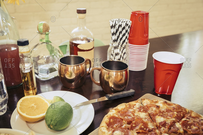 Pizza and ingredients for mixed drinks on a table at a party