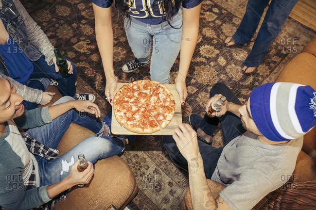 Friends having pizza and drinking at a party