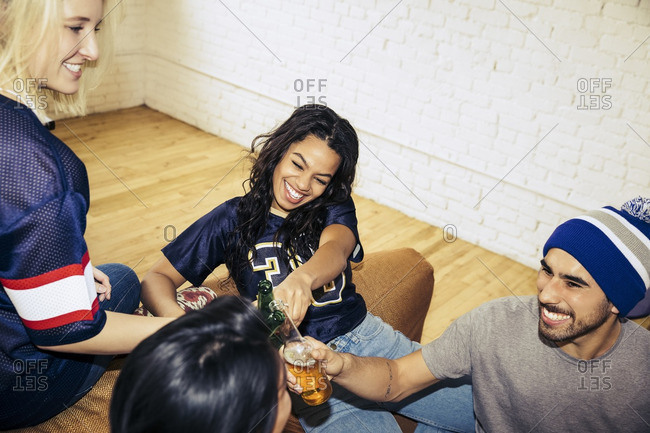 Friends in sports jerseys clinking beer bottles together at a party