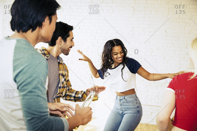 Friends standing around dancing and having fun at a party