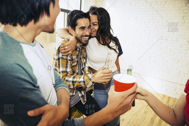 Friends hanging out and drinking together at a party