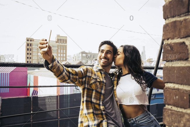 Couple standing on a balcony taking a selfie