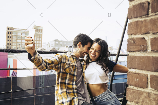Couple hanging out on a balcony taking a selfie