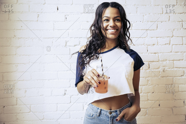 Young woman holding a mixed drink in front of a brick wall