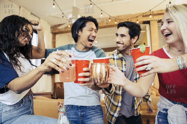 Four friends hanging out and drinking at a party