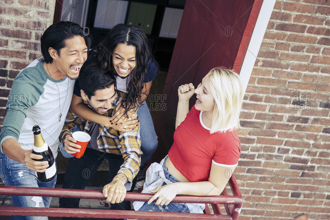 Four friends laughing and having fun on a balcony at a party