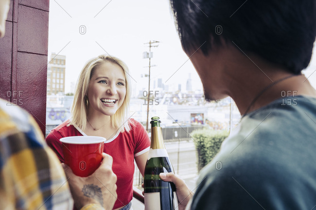 Friends having champagne on a balcony at a party