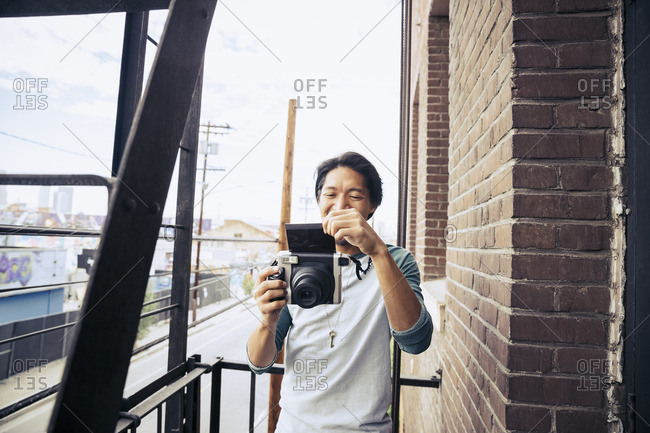 Man standing on a fire escape taking a photo with a vintage instant camera