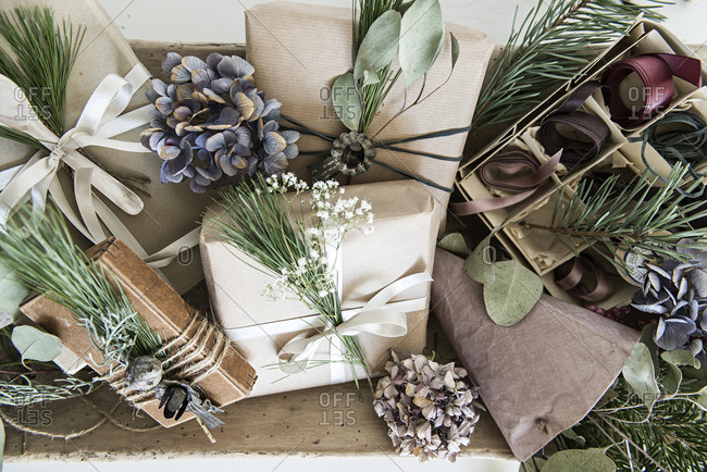 Gifts wrapped in paper and ribbon and decorated with pine branches