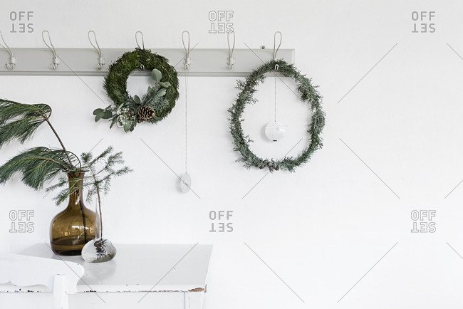 Wreaths hanging on hooks and pine branches in glass jars