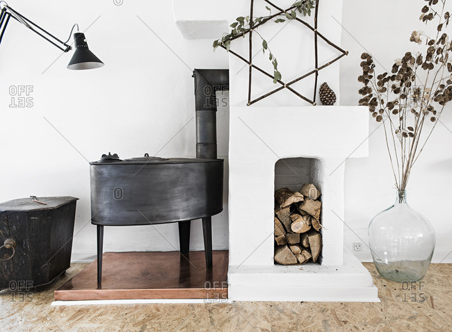 Wood stove and chopped wood in a white room