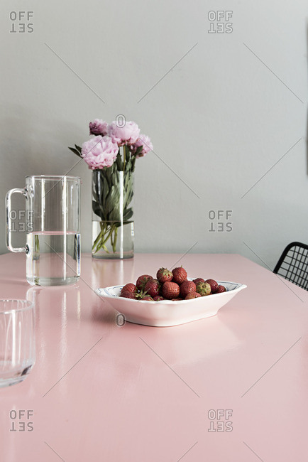 Pink table with peonies and strawberries