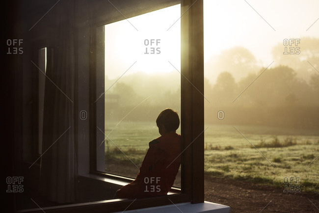 Boy looking out the window at a foggy sunrise in the morning