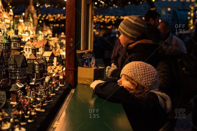 Girl looking at handmade ornaments at the Christmas market in Hamburg, Germany