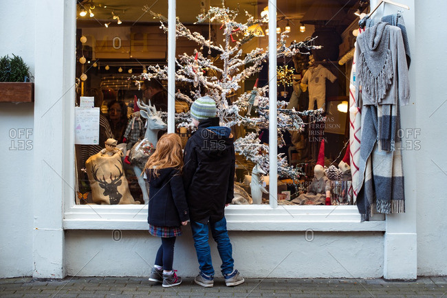 Cork, Ireland - 11/27/2016: Children on a street looking through a shop window with Christmas decorations