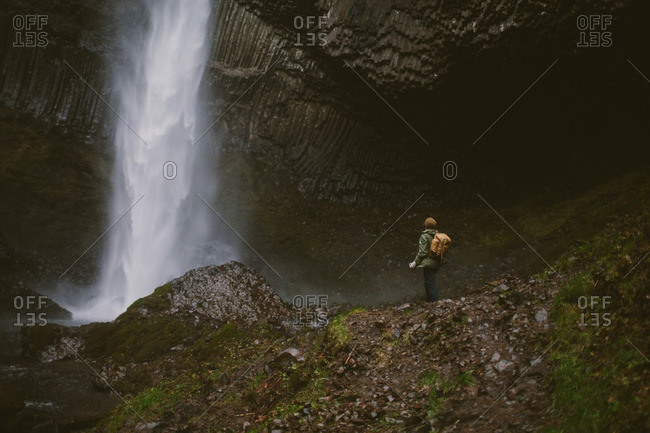 Man looking up at a waterfall