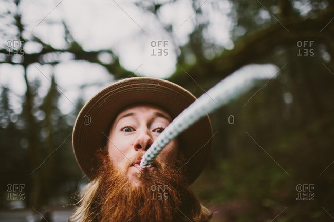 Man with beard blowing a party blowout