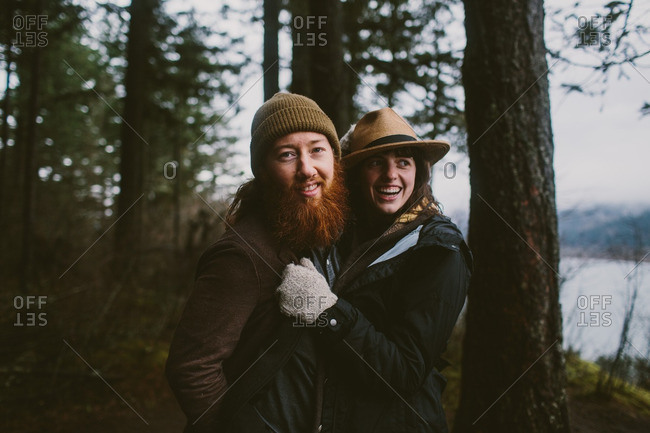 Happy couple standing in the woods