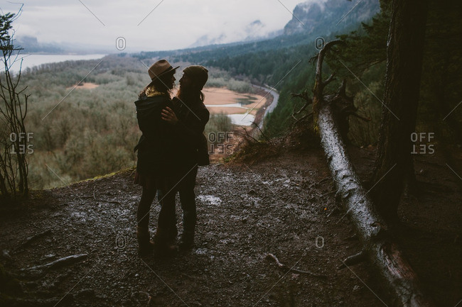 Silhouette of a couple standing in the wilderness preparing to kiss