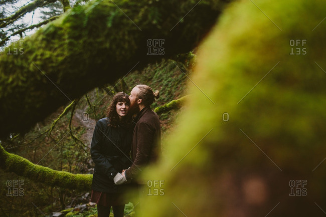 Couple standing by a mossy tree kissing