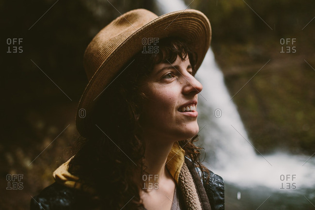 Portrait of a brunette woman with a hat standing by a waterfall