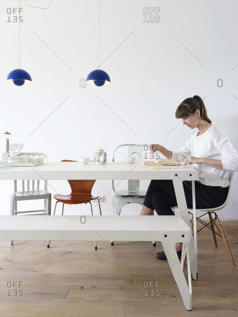 Woman sitting at dining room table doing a craft project