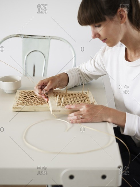 Woman weaving rattan whicker at a dining room table