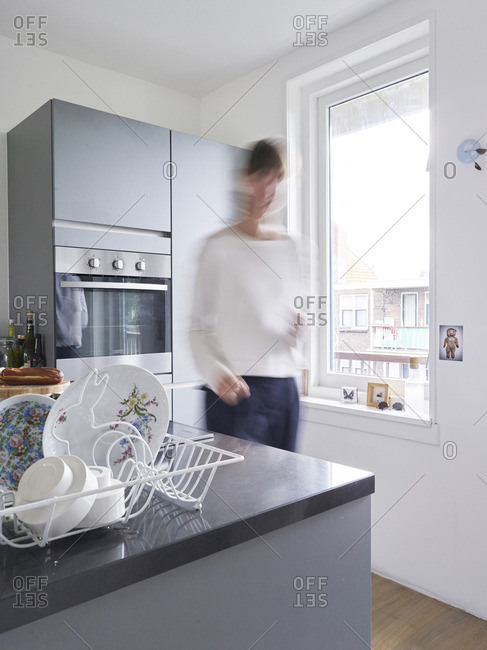 July 16, 2010: Blurred woman walking in kitchen with dishes in a basket on the counter
