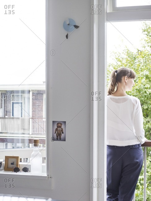 Rear view of a woman standing on her balcony