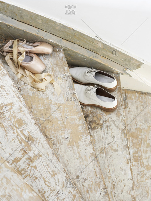 Pair of casual shoes and ballet slippers on old stairs
