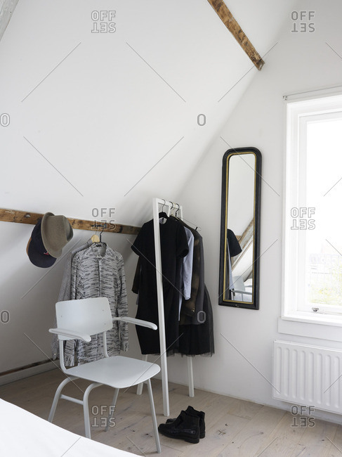 Clothes hanging on a rack and wooden board in a bedroom