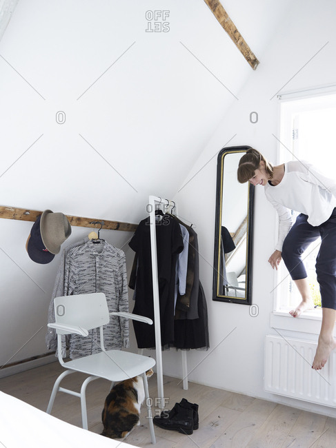 Woman climbing into window of her bedroom