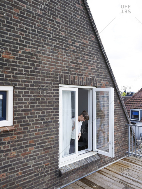 Woman looking out a window of her brick home