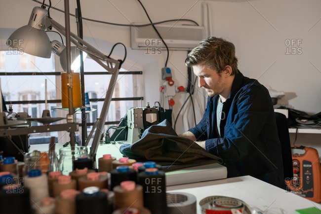 Young man sewing denim on a sewing machine