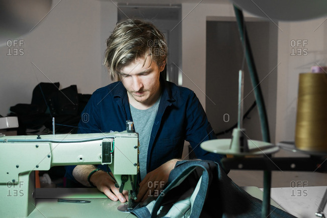 Young tailor sewing denim on a sewing machine