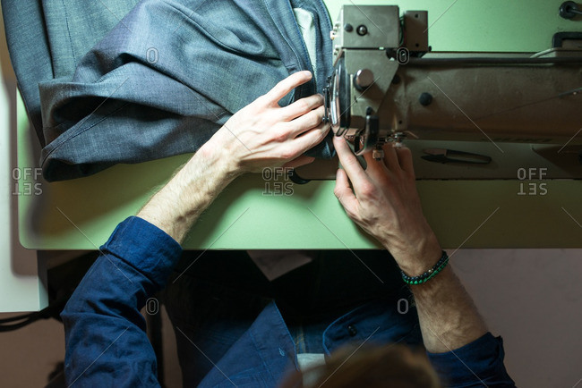 Overhead view of a tailor sewing denim on a sewing machine