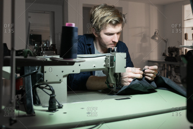 Young tailor sewing fabric on a sewing machine