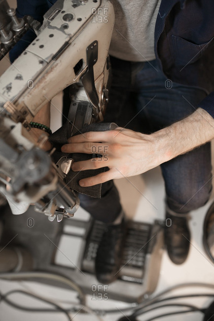 High angle view of a tailor sewing denim on a sewing machine